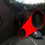 Is this a Ghost crossing the road in front of a busy tunnel?