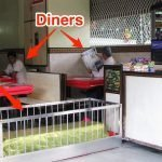 Diners at a restaurant in India eat their meals sitting at tables scattered between 12 coffins